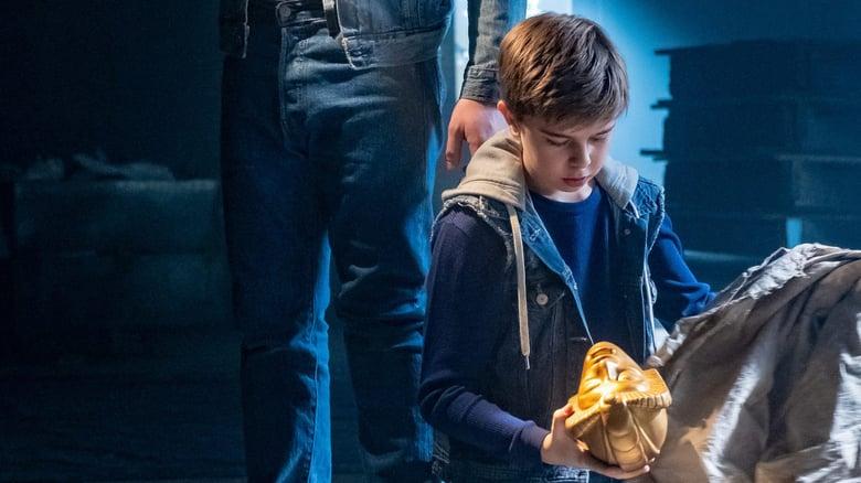 boy finding a golden statue head in a bag