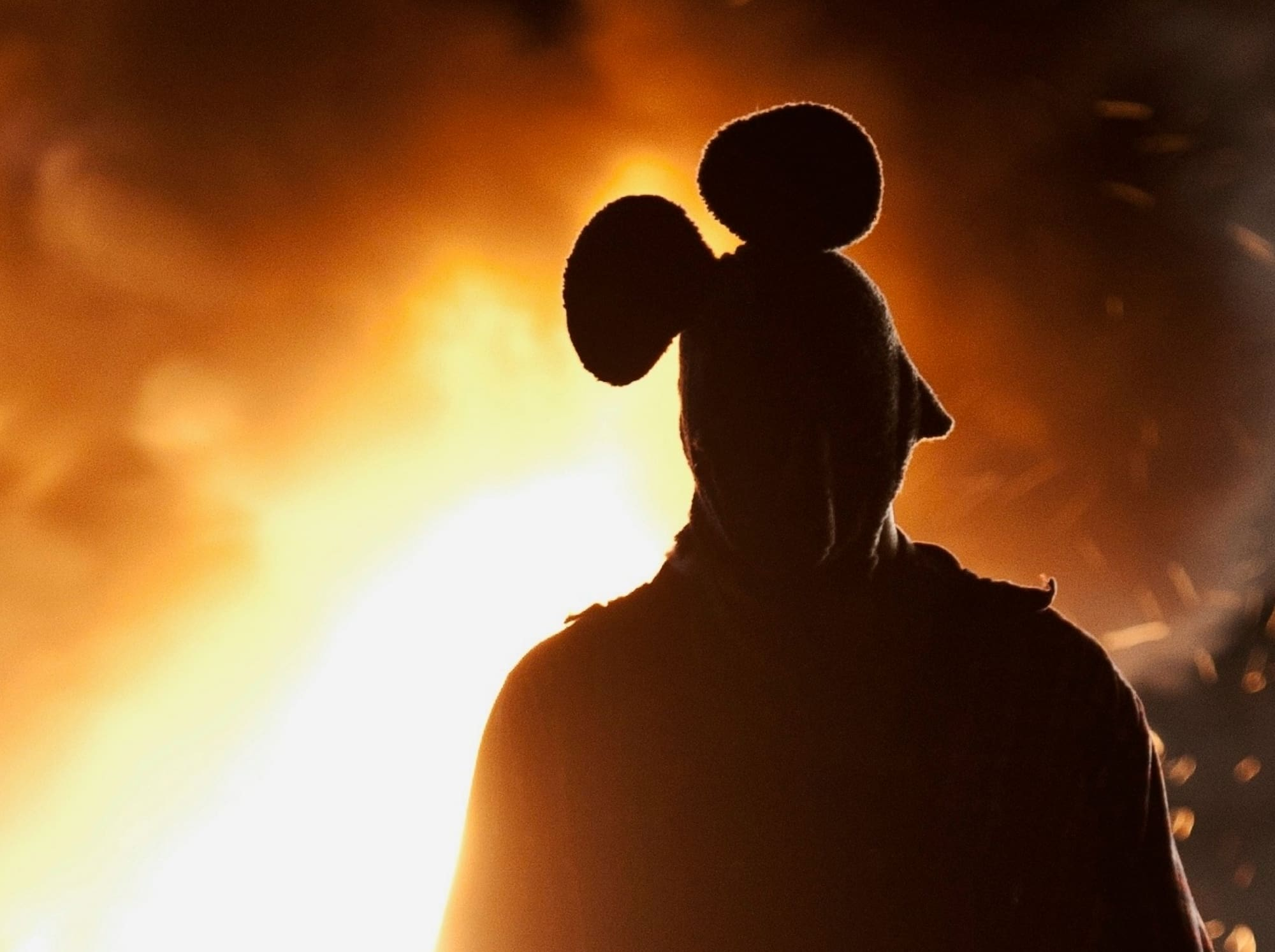 scary man in a mouse costume with fire in the background