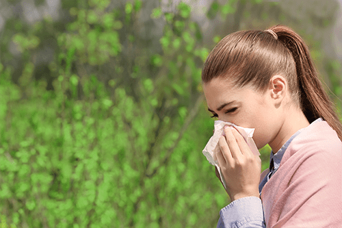 Woman suffers from allergies outdoors