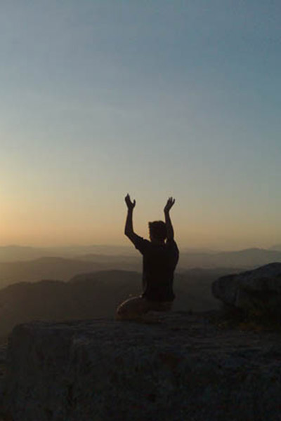 man practicing yoga on a mountian top facing the sun