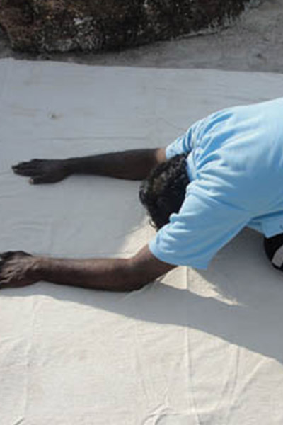 man with his hands on the ground as he bends forward in a yoga stretch
