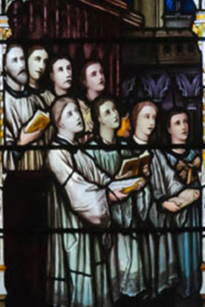 stained glass picture of saints praying