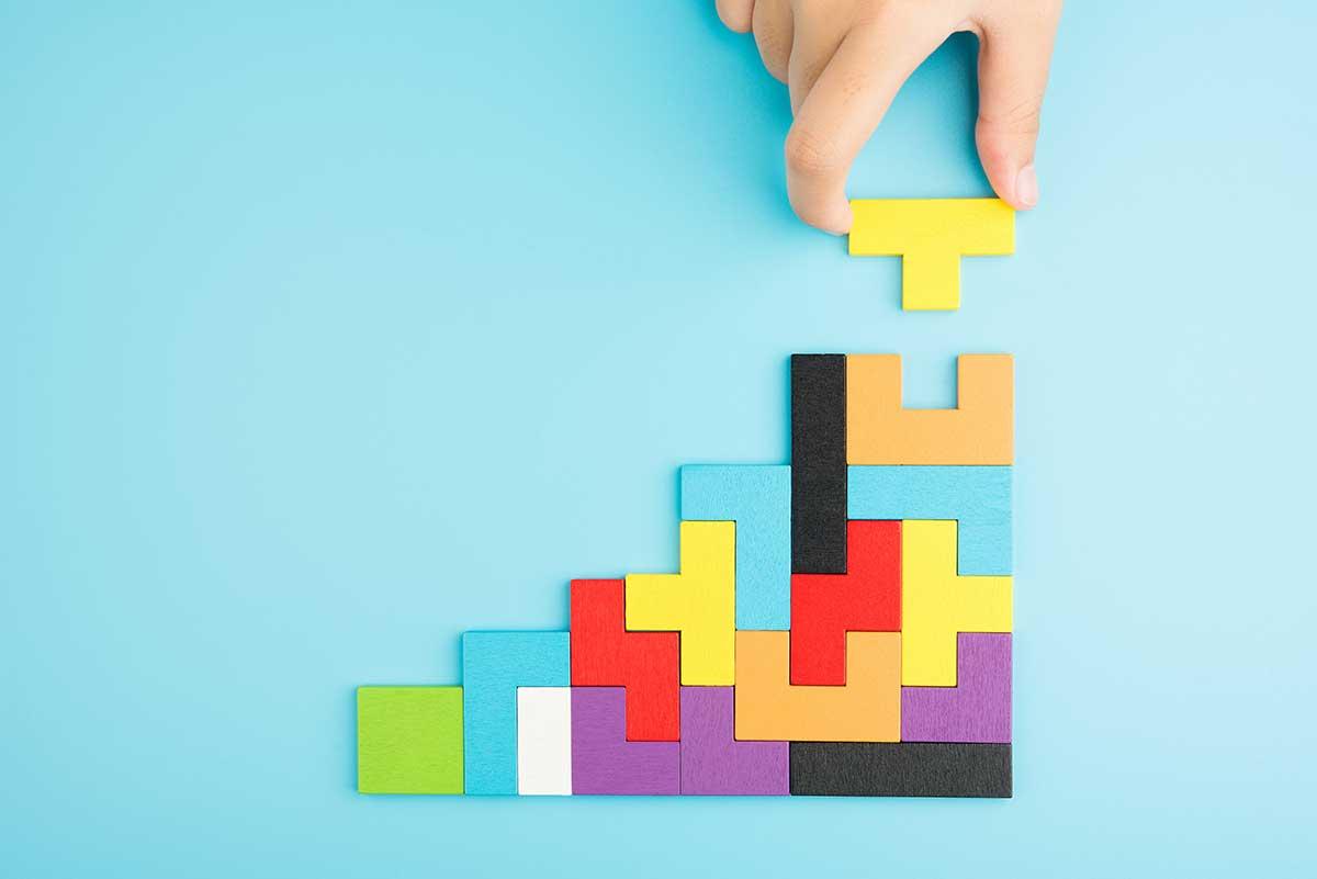 Foto de diversas peças de um quebra-cabeça formando um gráfico financeiro