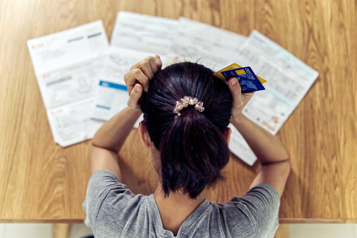 Foto de uma pessoa segurando cartões e olhando para contas a pagar em cima da mesa