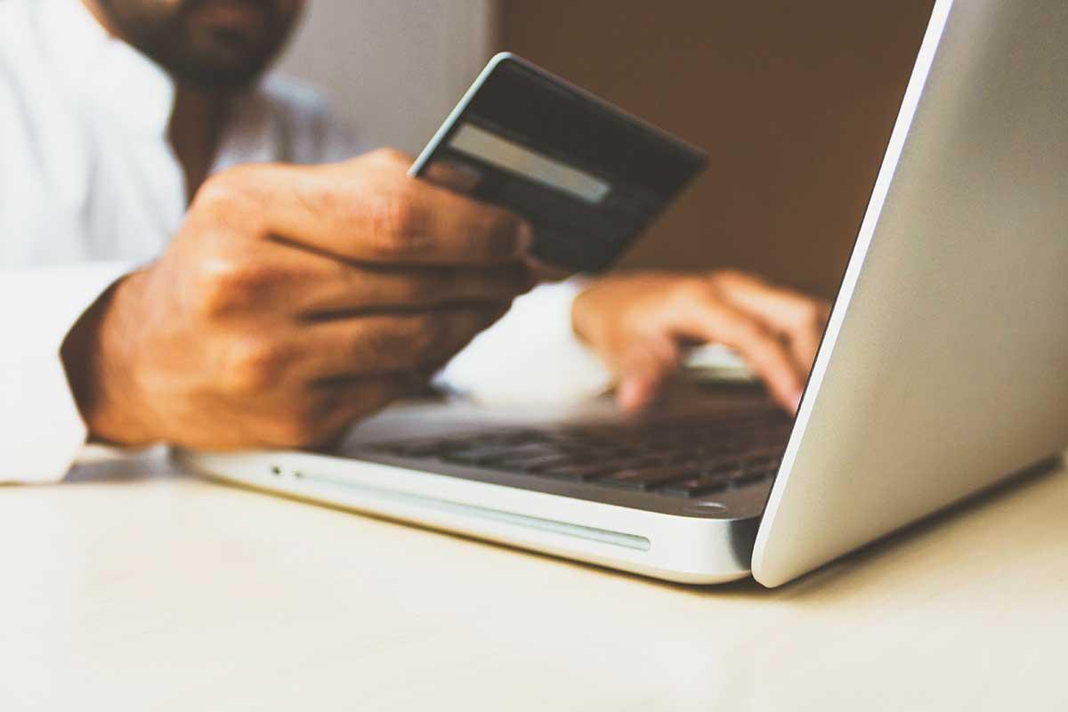 Foto de uma pessoa segurando um cartão de débito/crédito em frente a um notebook.