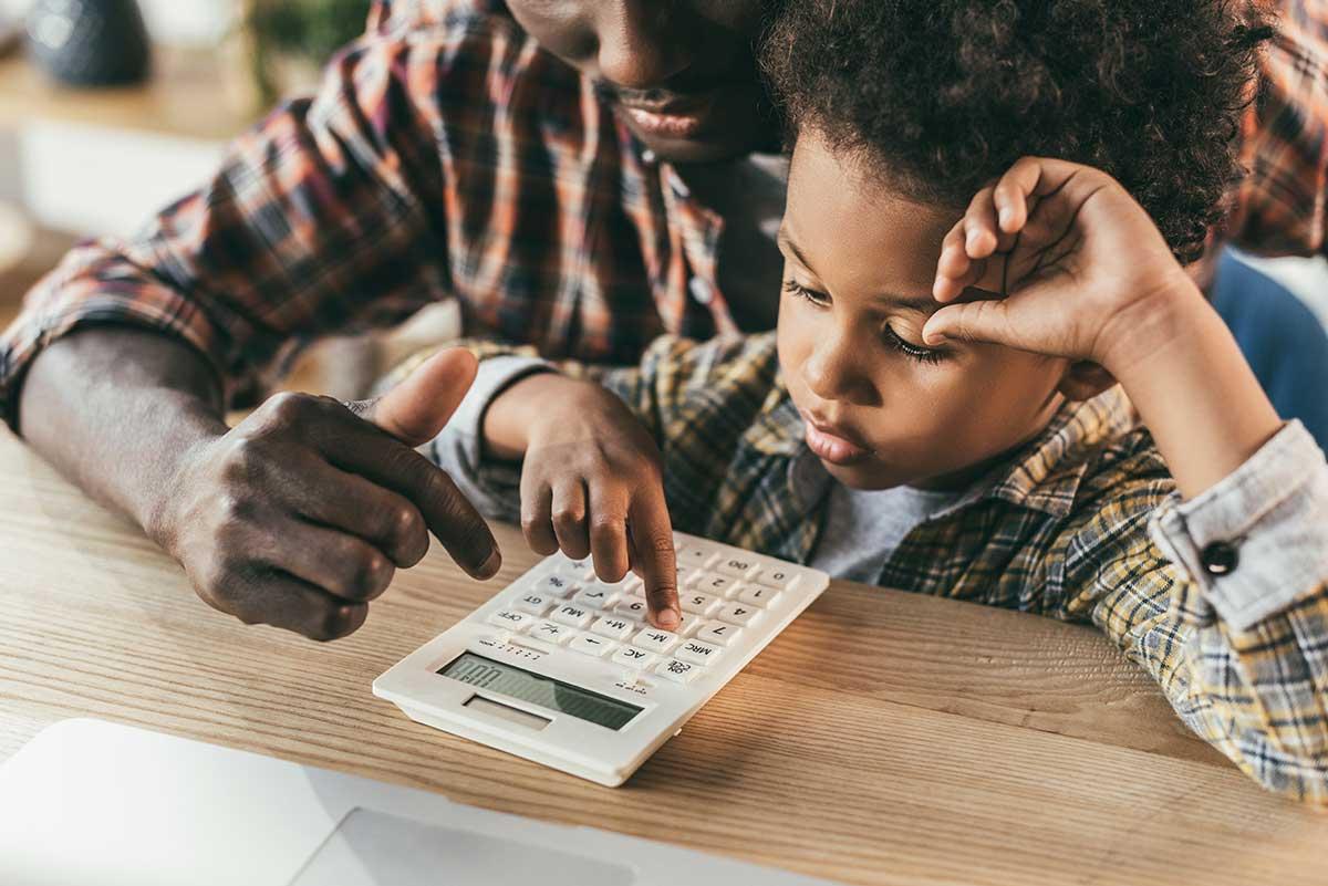 Foto de um adulto ensinando uma criança a usar uma calculadora