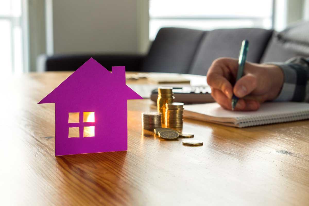 Foto uma uma pessoa em uma mesa fazendo contas em um caderno. Em frente há uma casa de papel recortado.