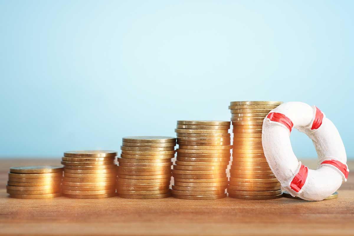 Foto de uma pilha de moedas sobre uma mesa e uma boia salva-vidas em miniatura.