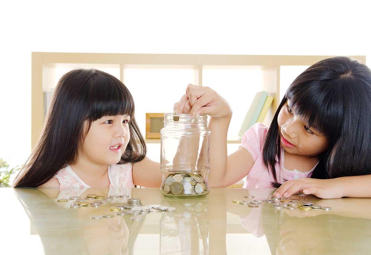 Foto de duas crianças colocando moedas em uma jarra de vidro.