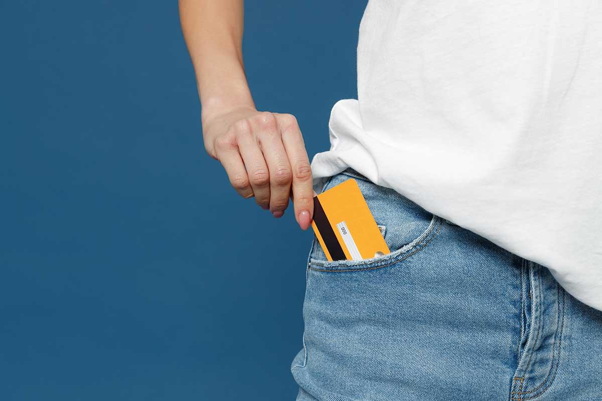 Foto de uma pessoa colocando um cartão bancário no bolso.