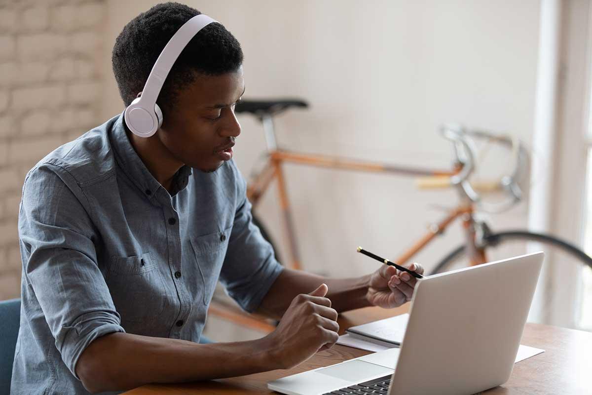 Foto de um jovem negro em frente ao computador, usando um fone de ouvido.