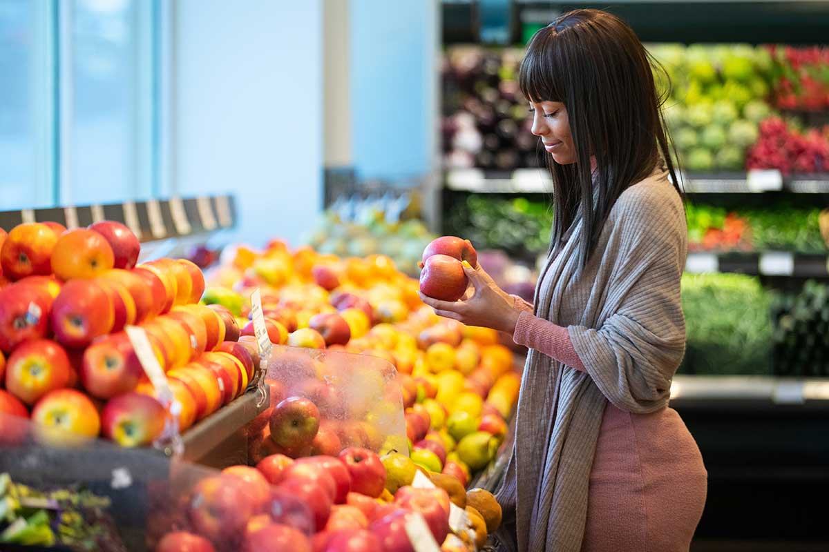 Foto de uma mulher escolhendo produtos em um supermercado.