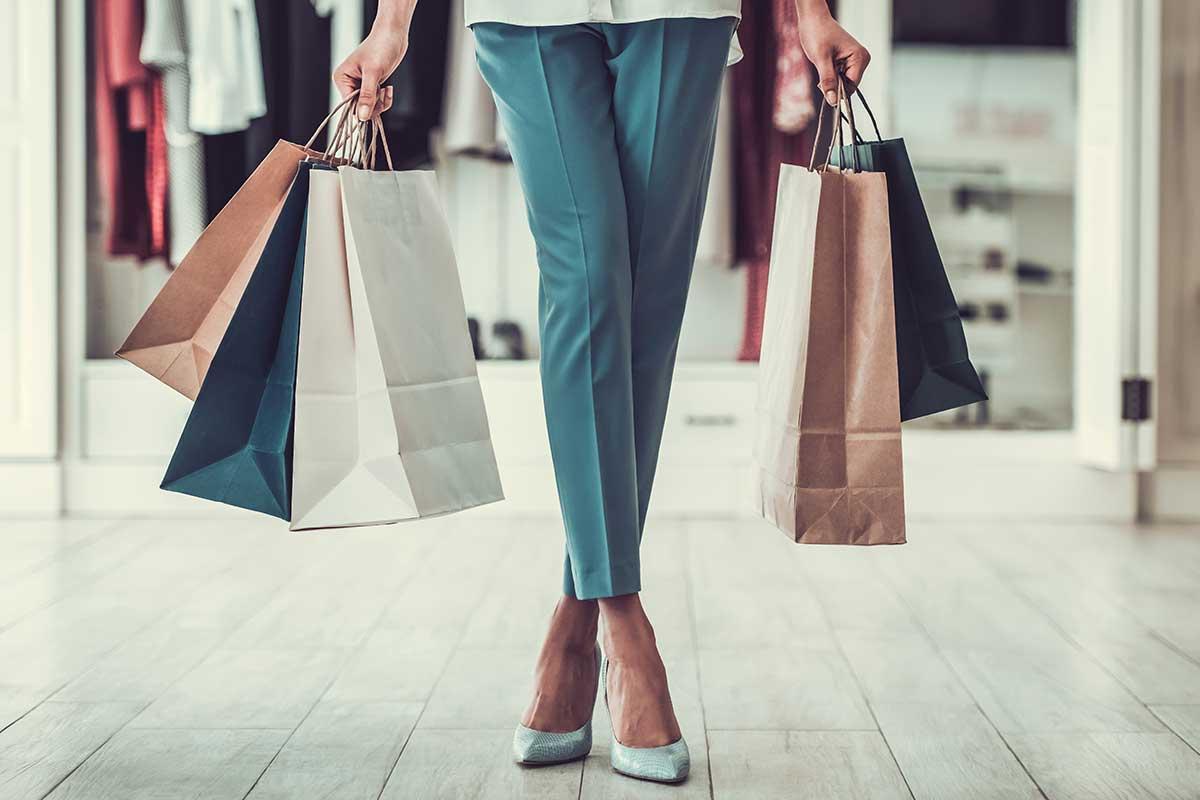 Foto de uma mulher segurando sacolas de compras.
