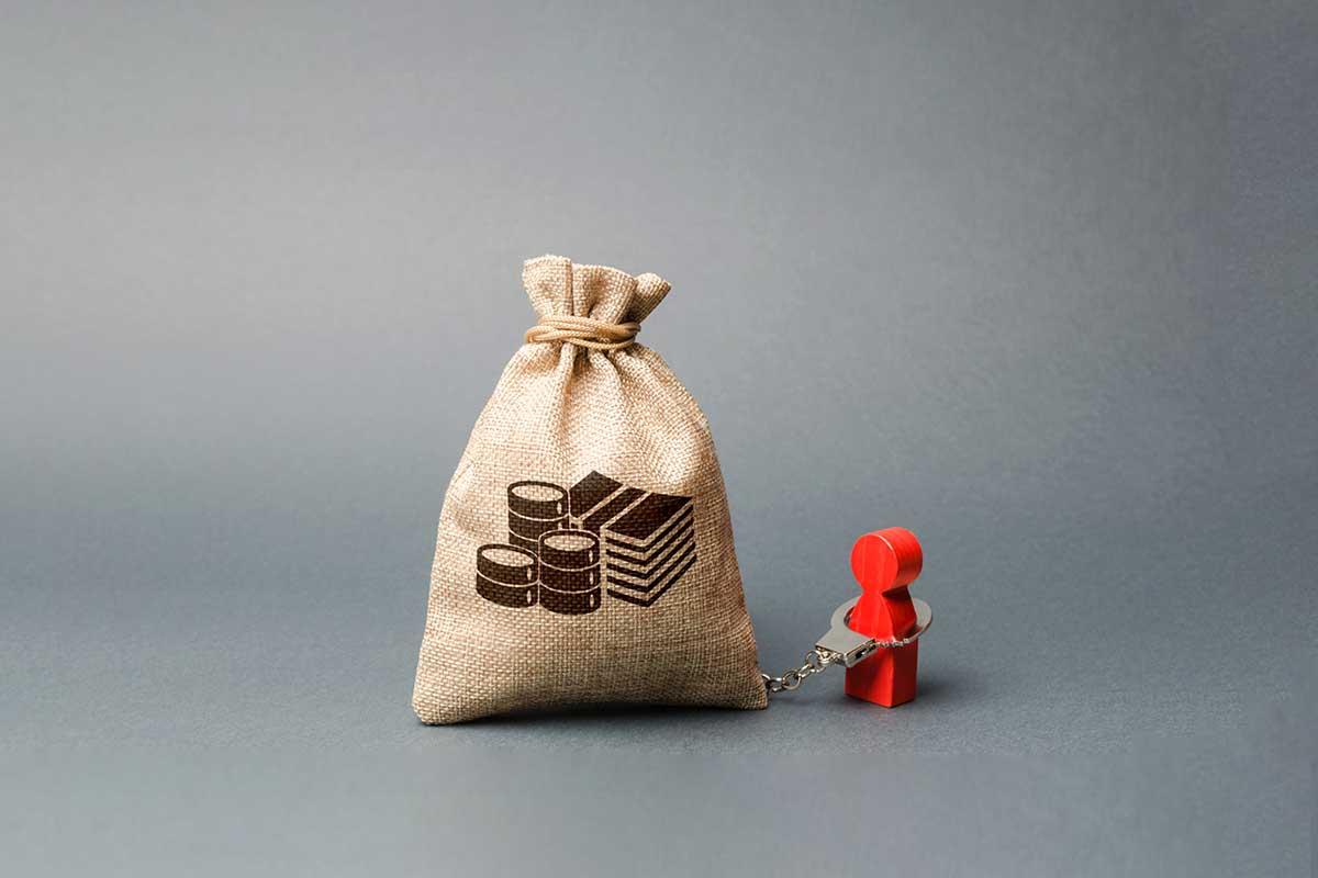 Imagem de um boneco algemado a um saco de dinheiro.