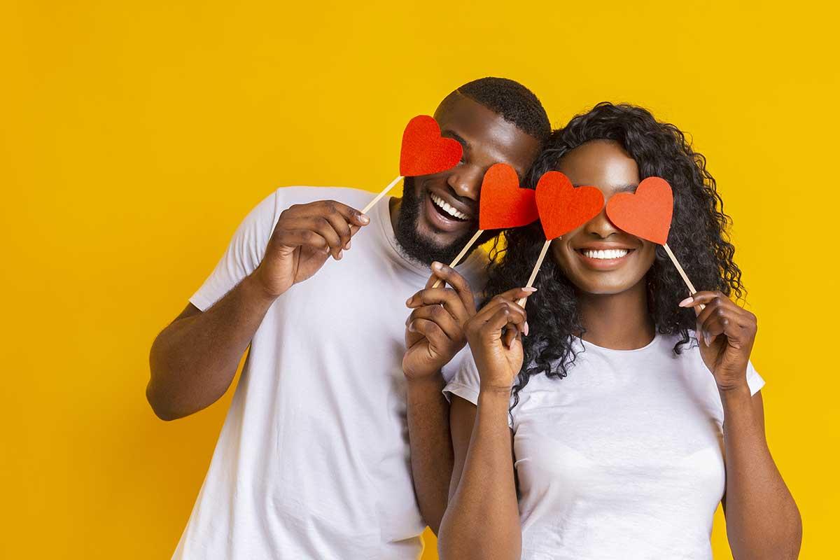 Imagem de um casal segurando corações de papel