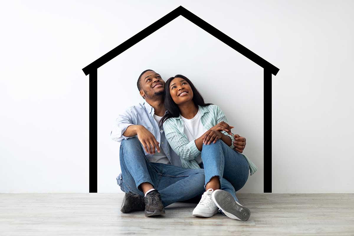 Imagem de um casal sentado, olhando para cima, imaginando uma casa.