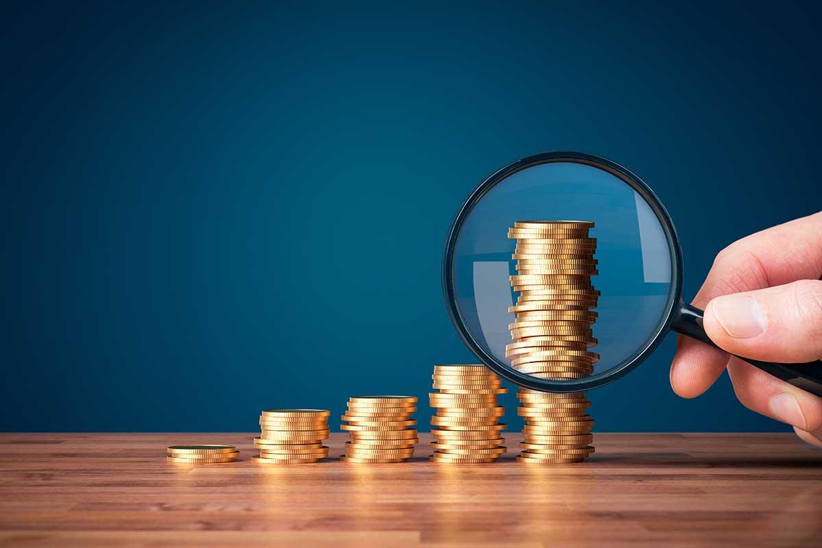 Imagem de uma pessoa segurando uma lupa em frente a uma pilha de moedas.