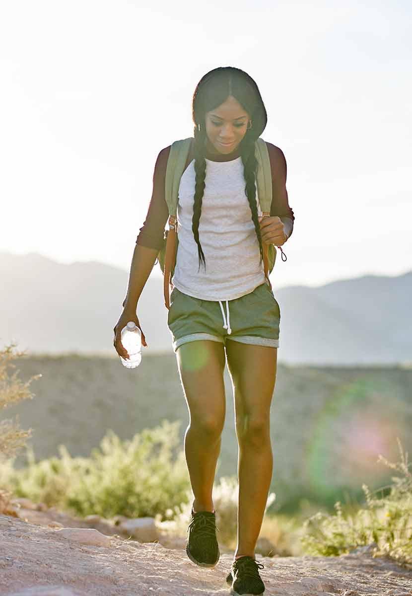 Foto de uma mulher negra caminhando em uma trilha