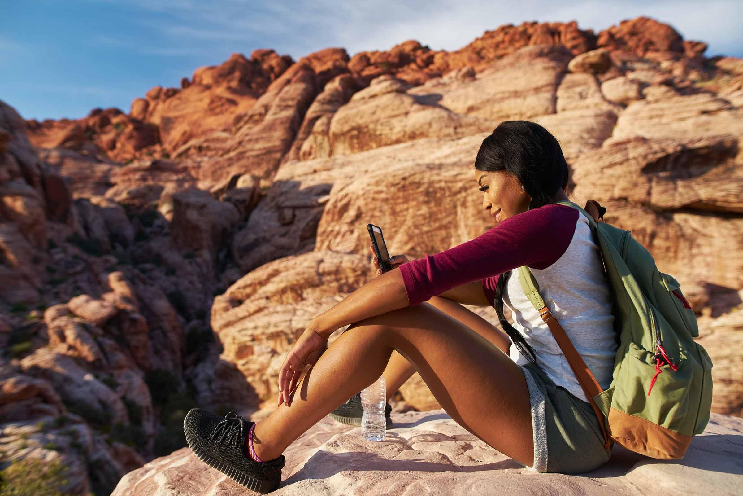 Foto de uma mulher negra sentada em uma pedra, olhando seu smartphone