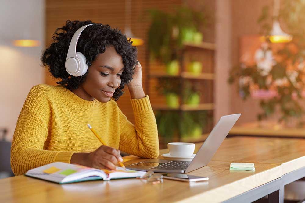 Uma mulher negra, em frente a um notebook, assistindo a um workshop online.