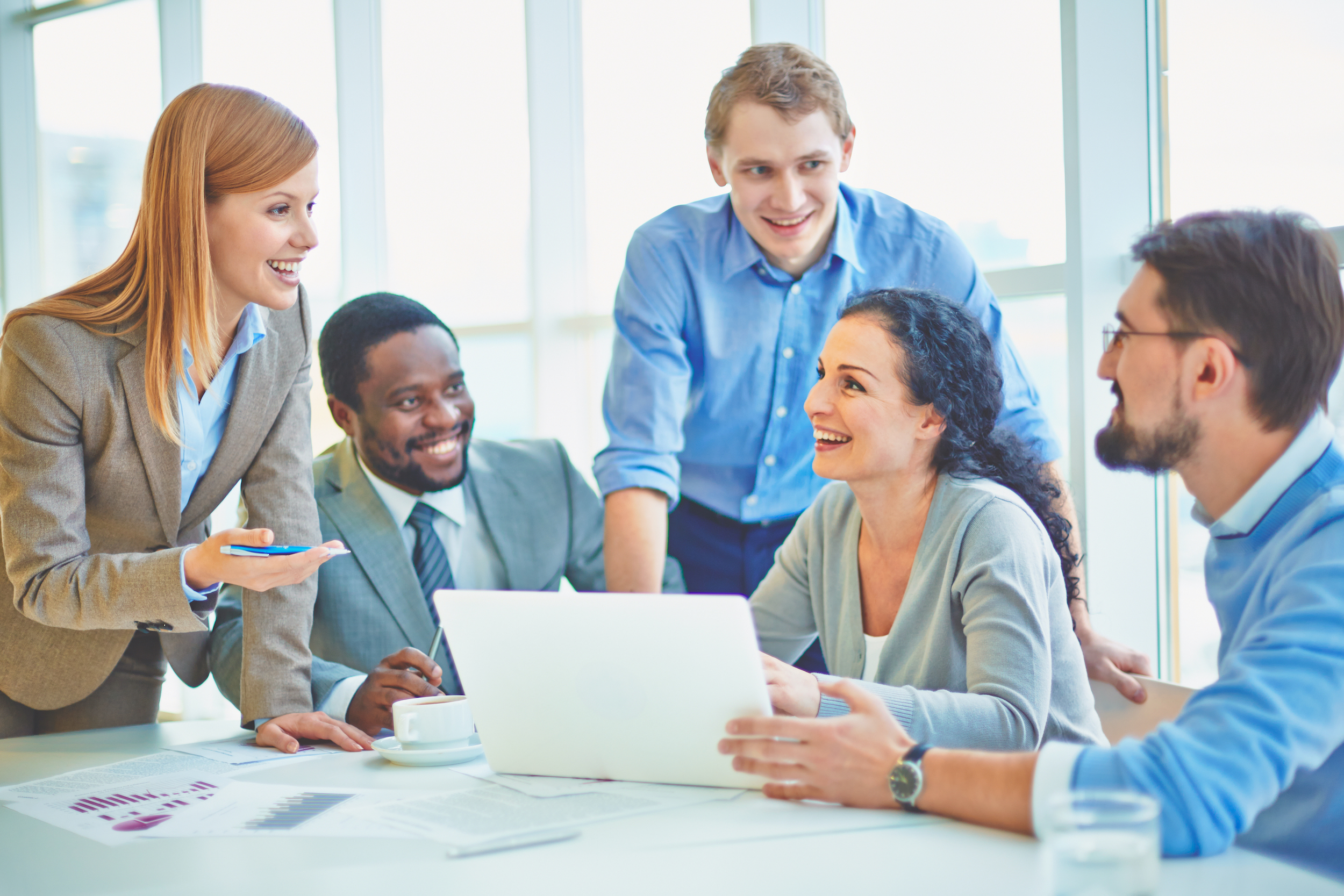 People in office happily discussing around a laptop
