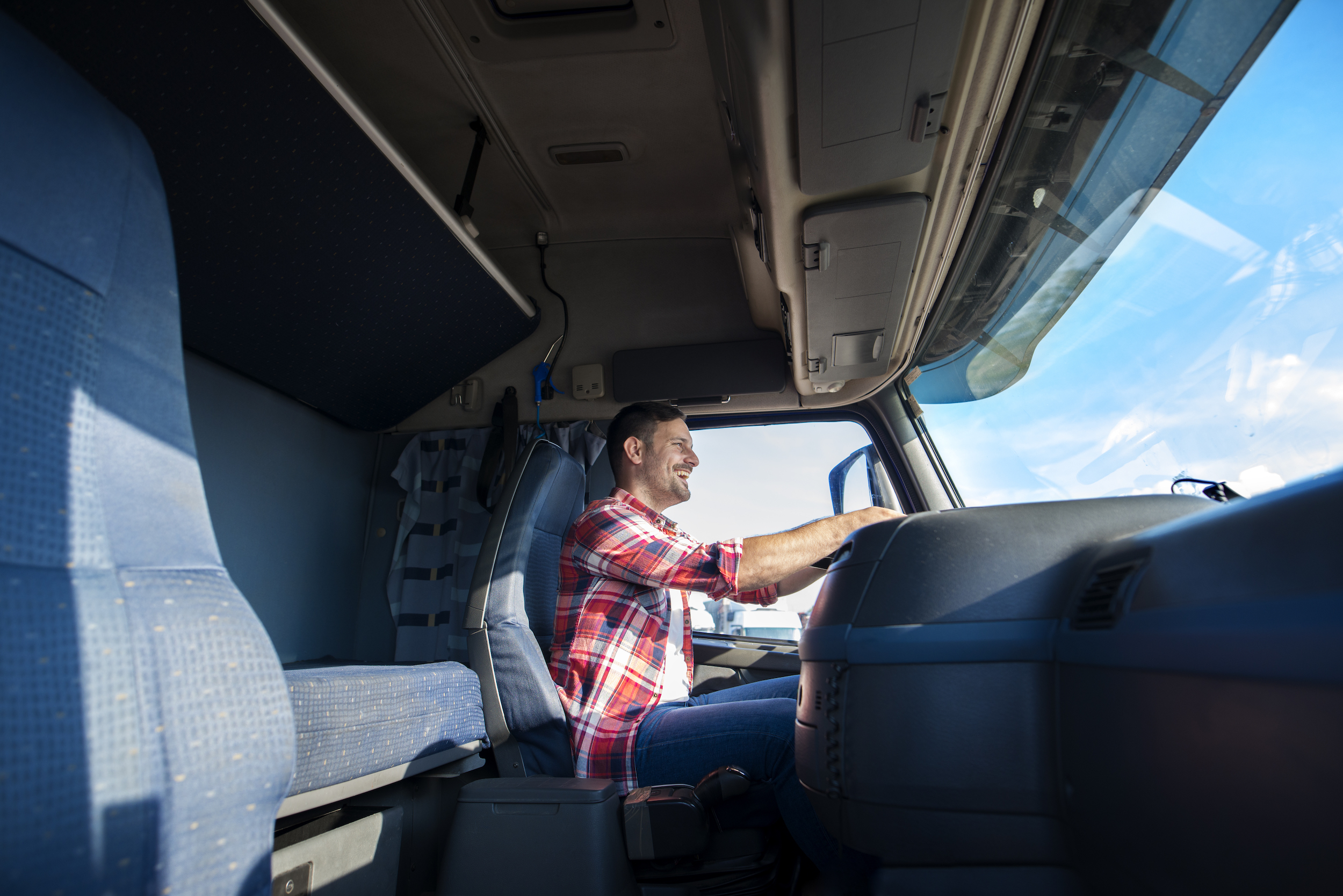 professional truck driver in cab, smiling whilst driving