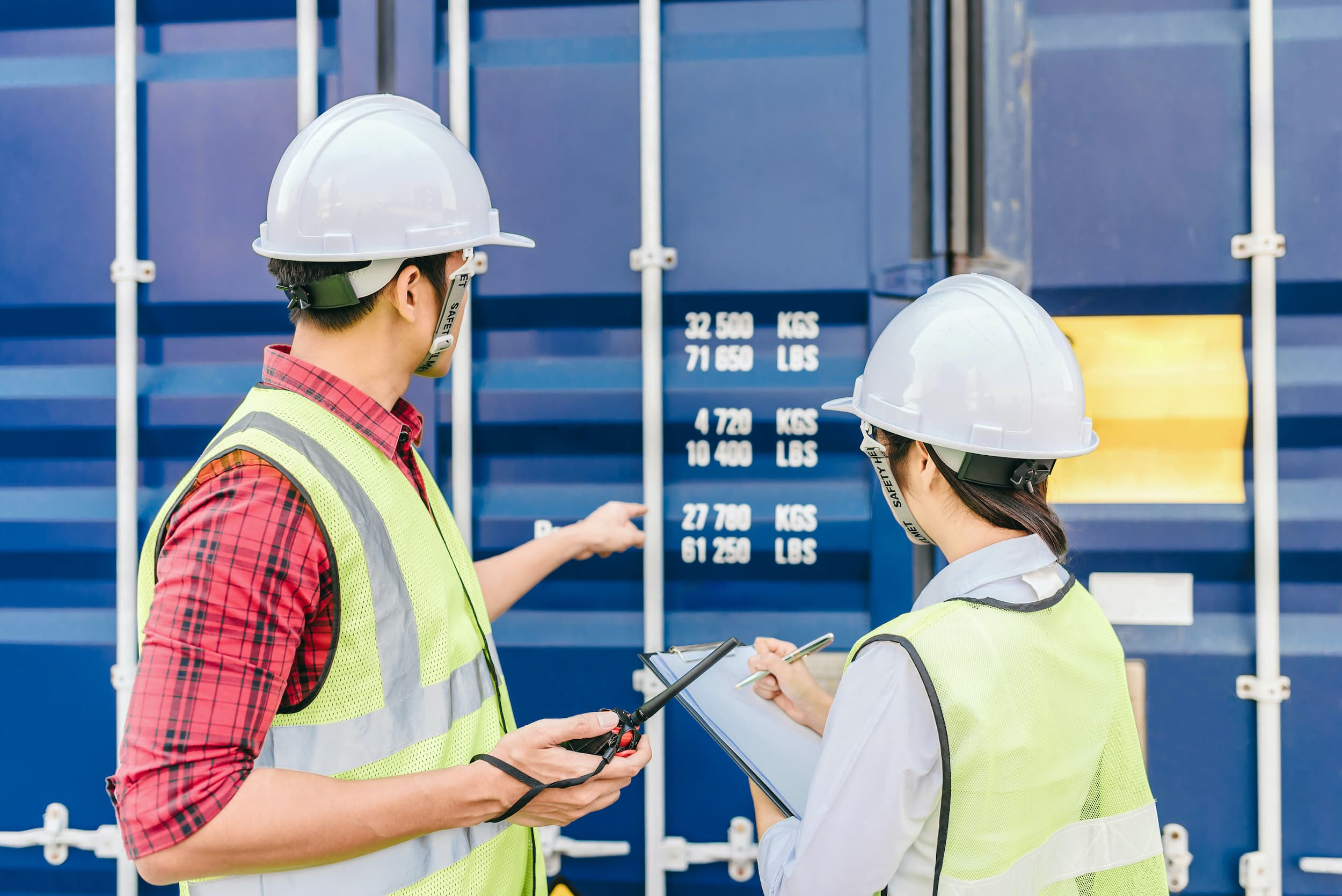Foreman and staff checking shipping container details