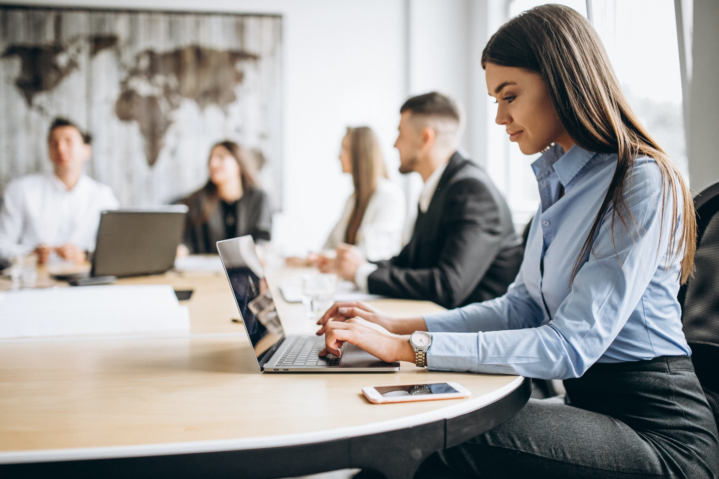 Female employee in office using laptop at table