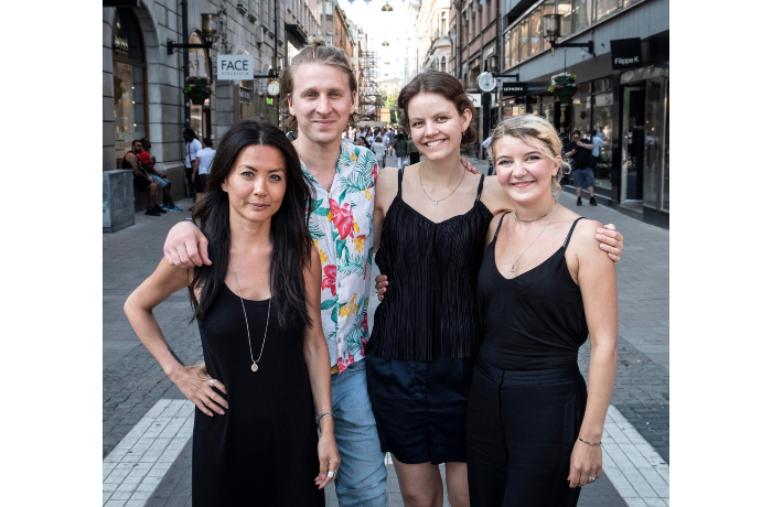 Photo of three women dressed in black and a man in a flowery shirt standing in the middle of a street