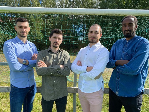Portrait of four men wearing shirts, standing in front of a football goal with arms crossed in front of them