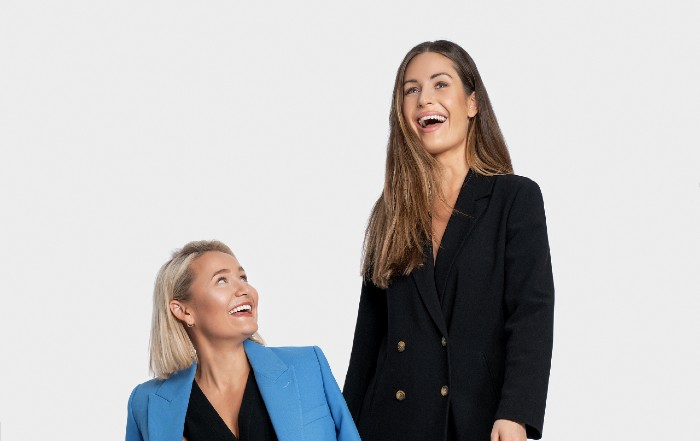 Portrait of two women, one in a blue and one in a black suit, laughing