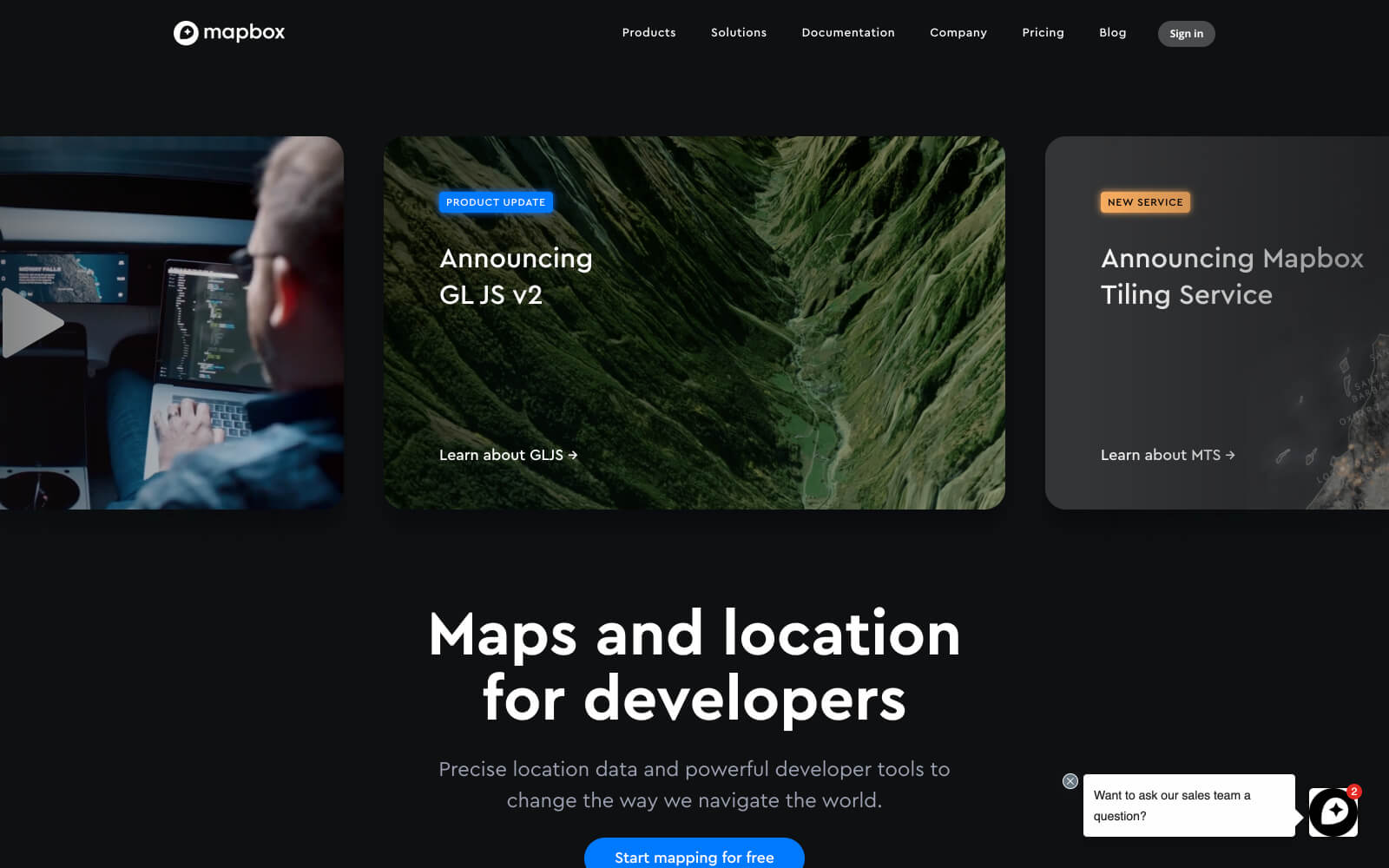"""The Mapbox website utilizes a large statement of """"Maps and location for developers"""" below sliding cards announcing product updates and news against a black background."""