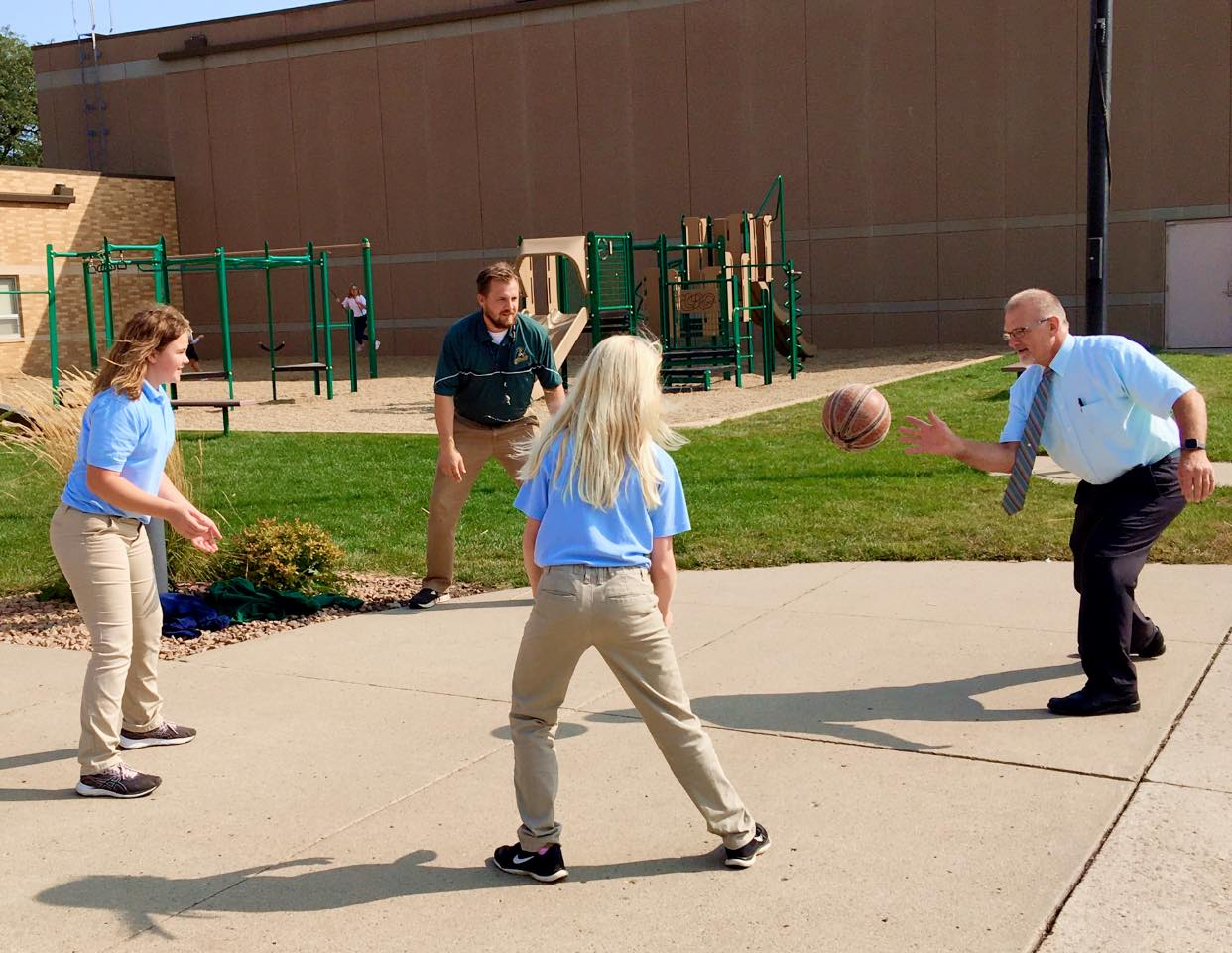 staff playing 4 square with elementary students
