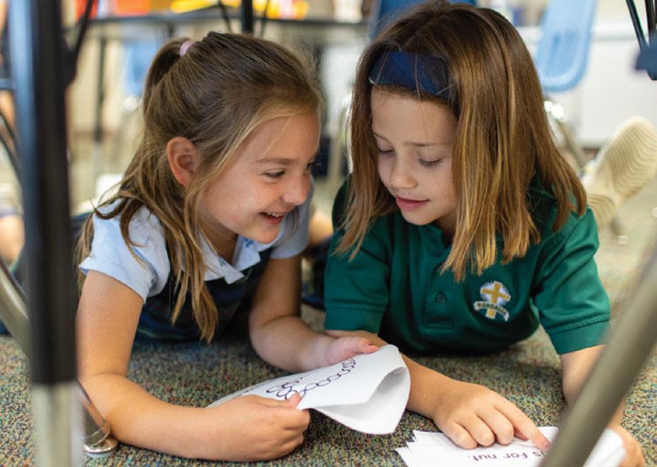 two kindergarten girls reading books