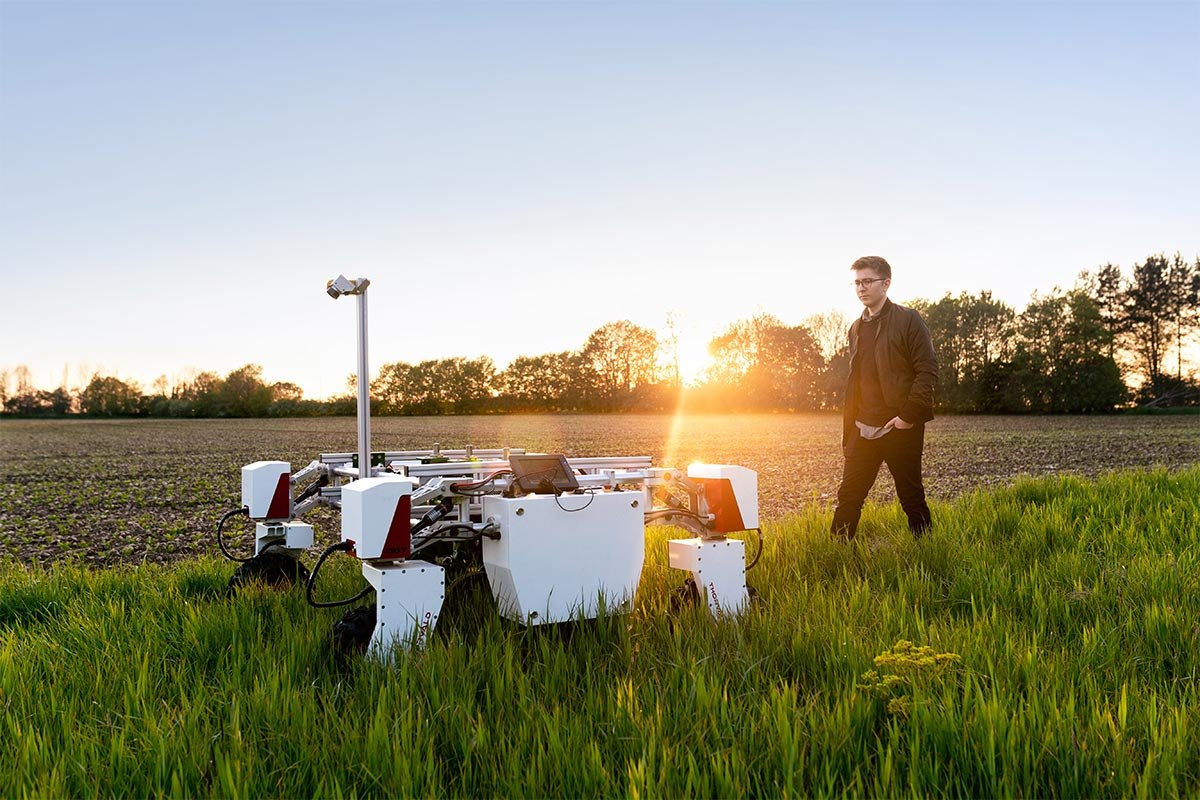 Man in a field with robotics equipment.
