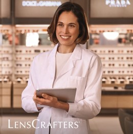 Doctor holding a tablet in the entrance of a Lenscrafters store