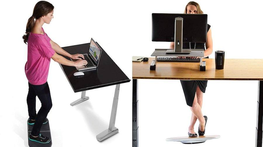 two women using balance boards at stand up desk in office