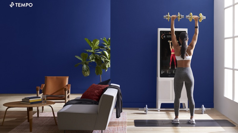 A woman lifting weights while working out in front of the Tonal home gym.