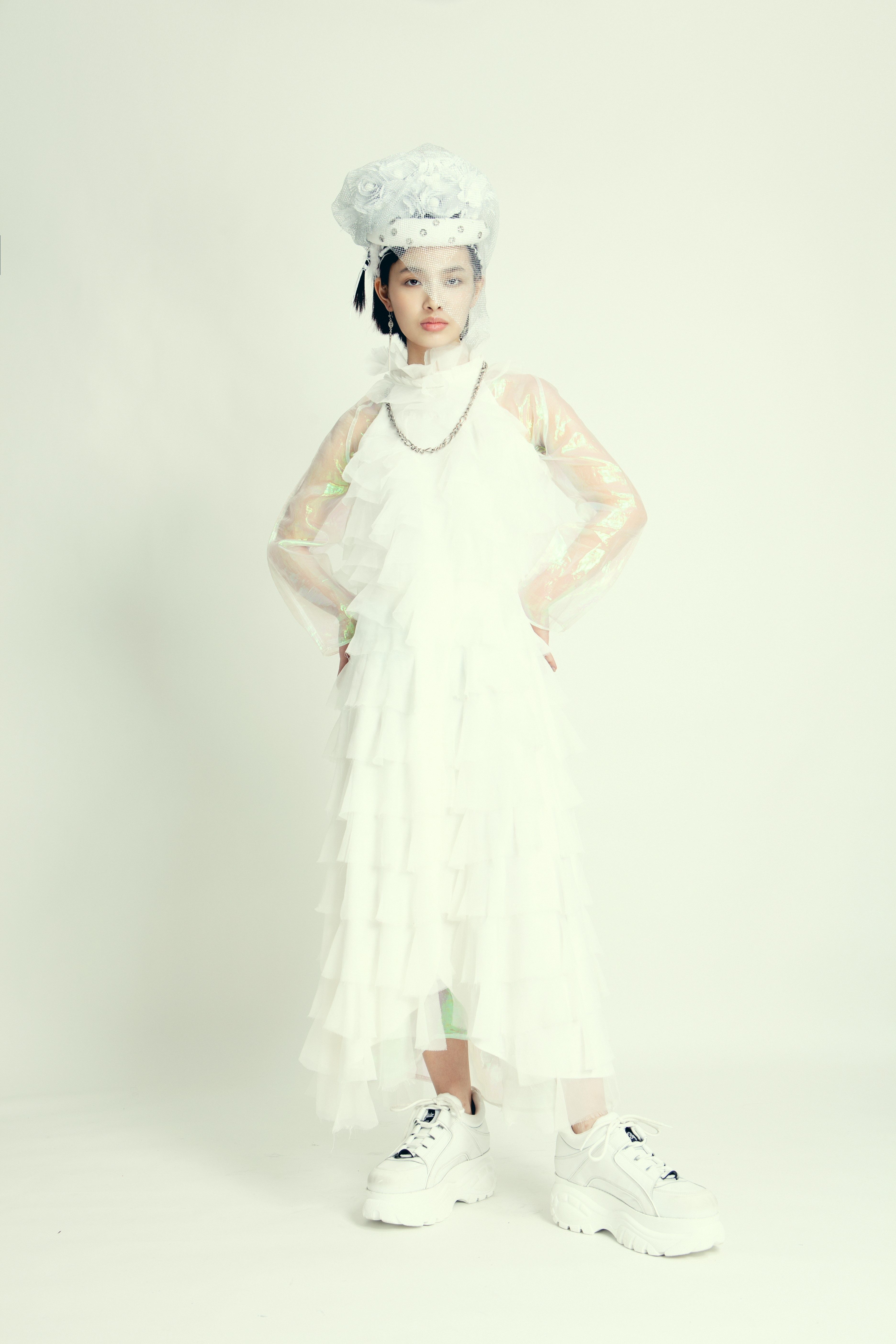White headpiece with silver embellishment : Seyit Ares  White tiered chiffon dress : Chaussettes Orphelines Organza iridescent long dress : Noémie Devime  White sneakers : Buffalo  Silver chain : stylist own
