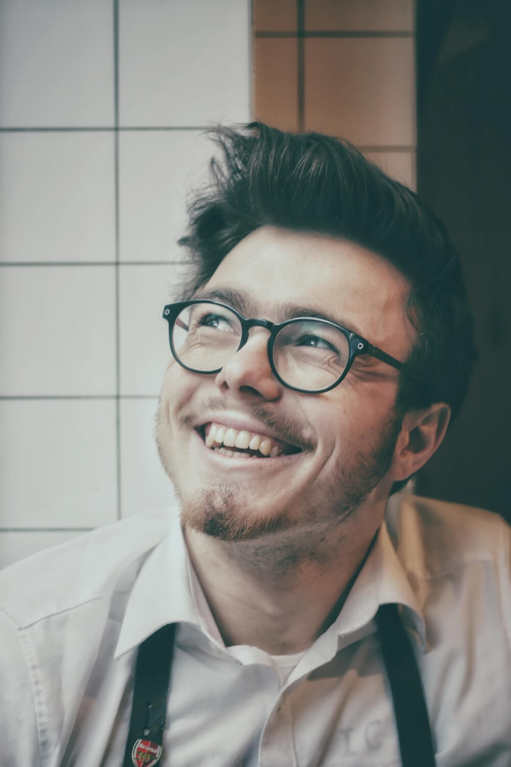 young man smiling with glasses