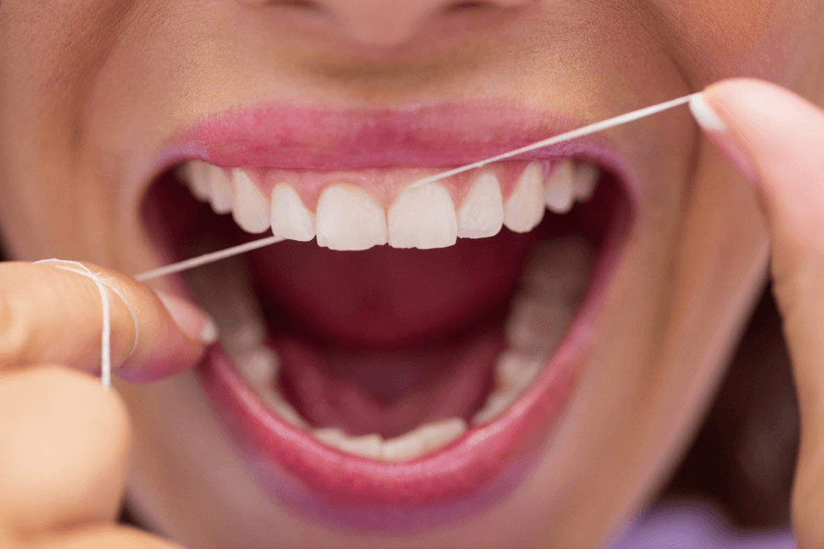 Person flossing their teeth with a perfect smile