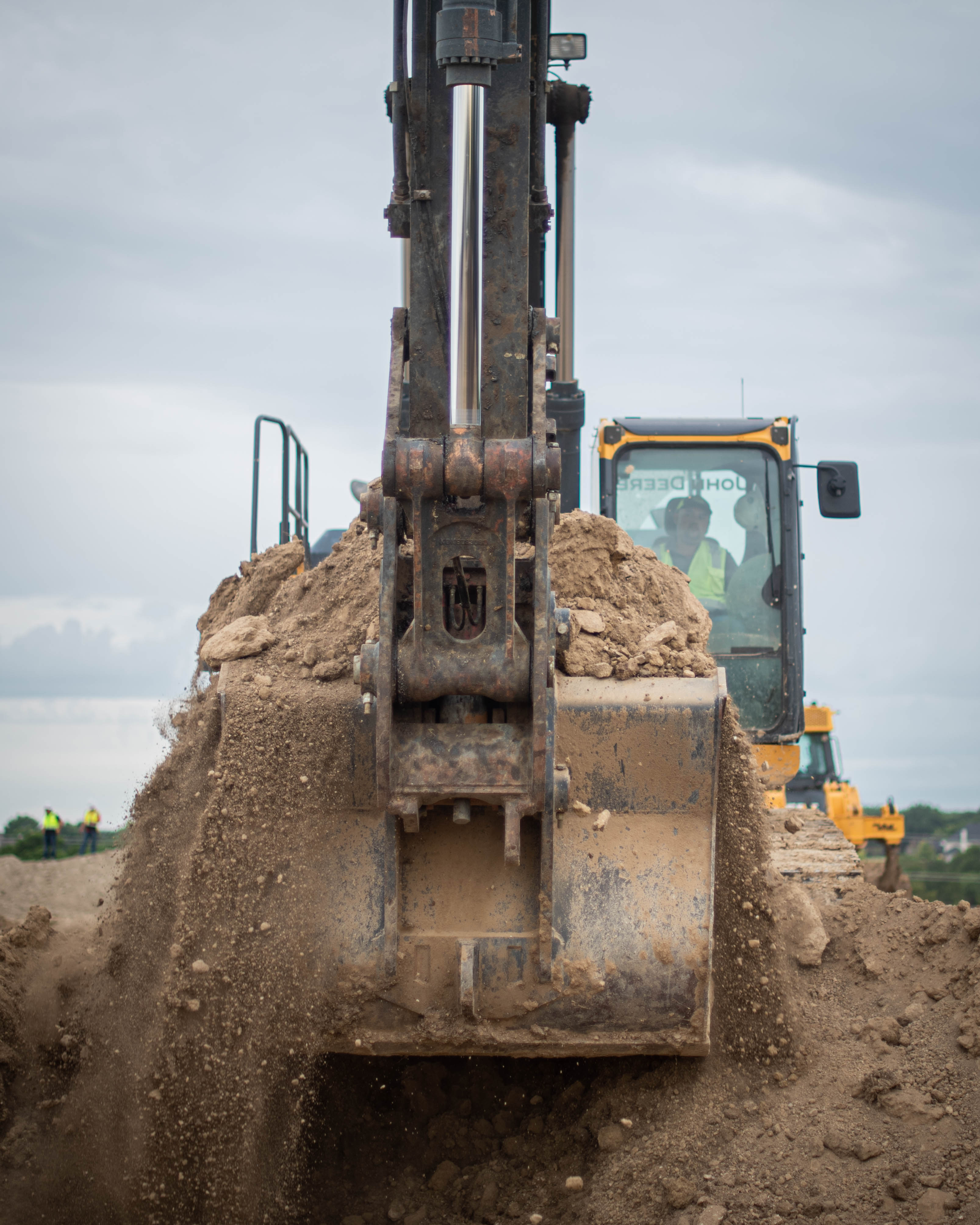 John Deere excavator digging dirt.