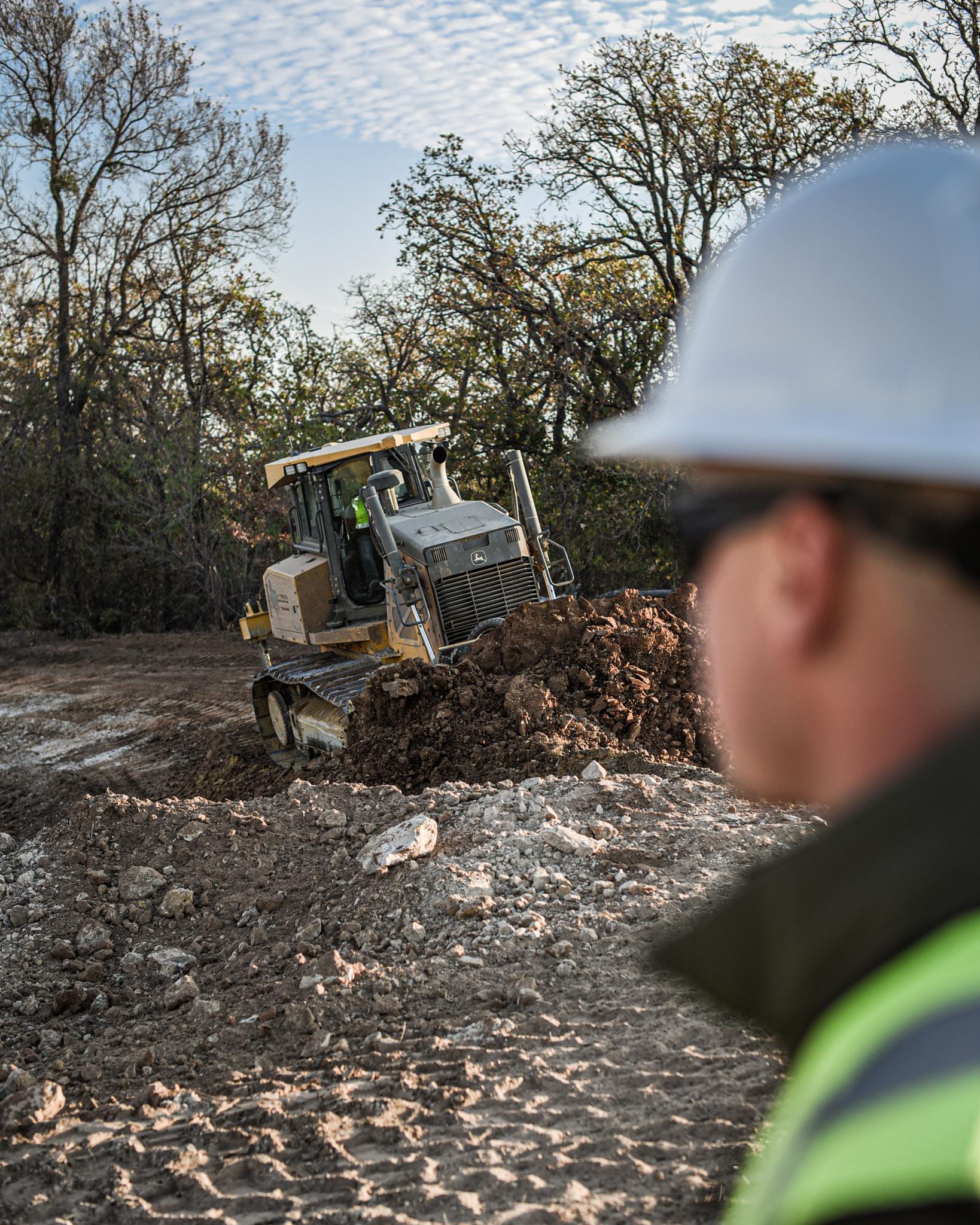 John Deere front loader clearing a job site.