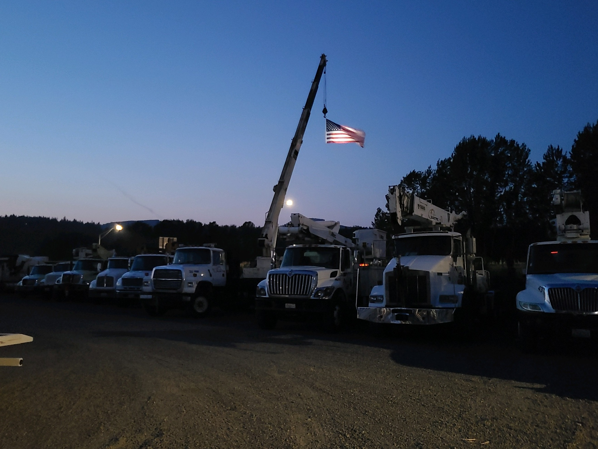 Industrial electric company fleet trucks with American flag
