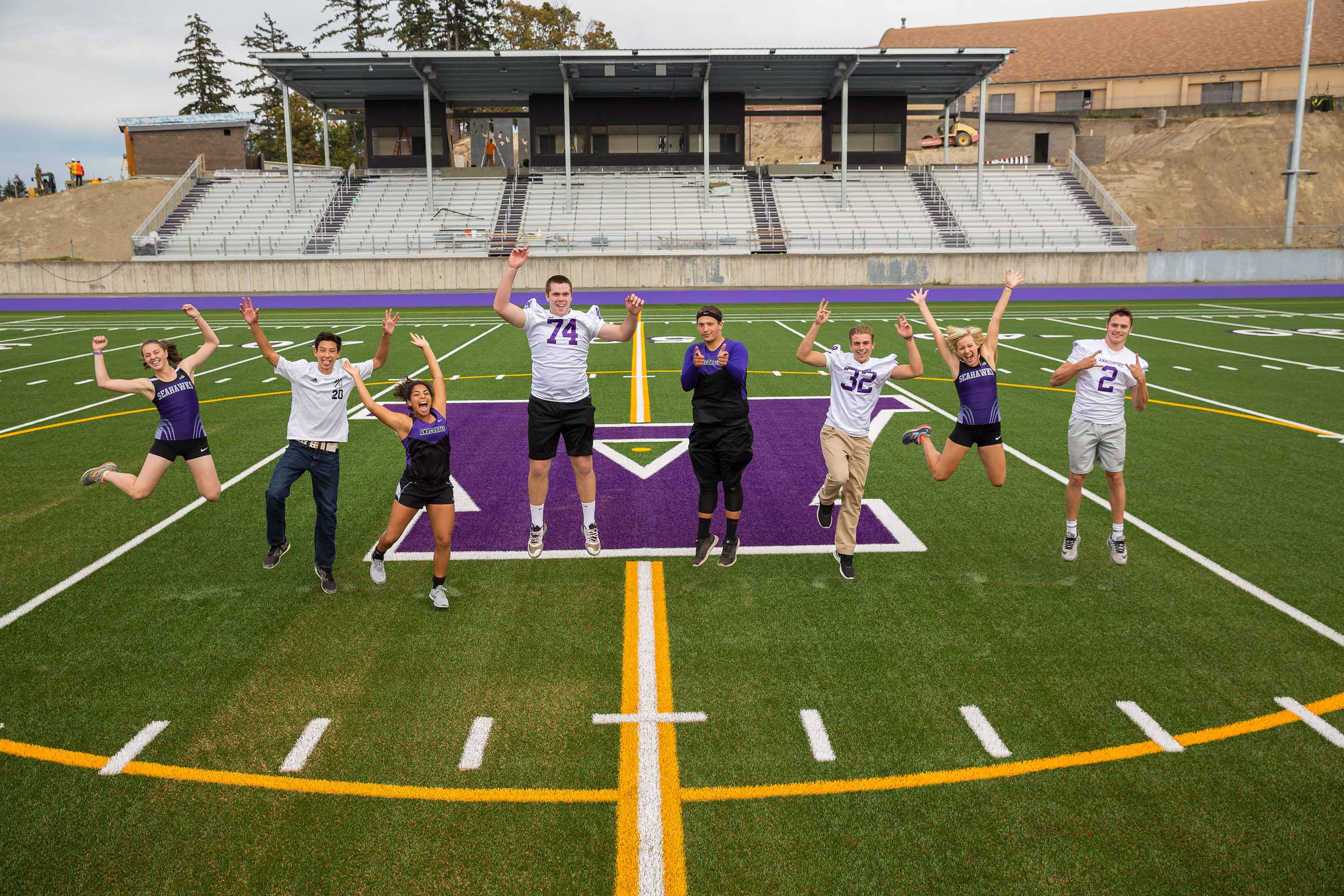 Students jumping on the football field.