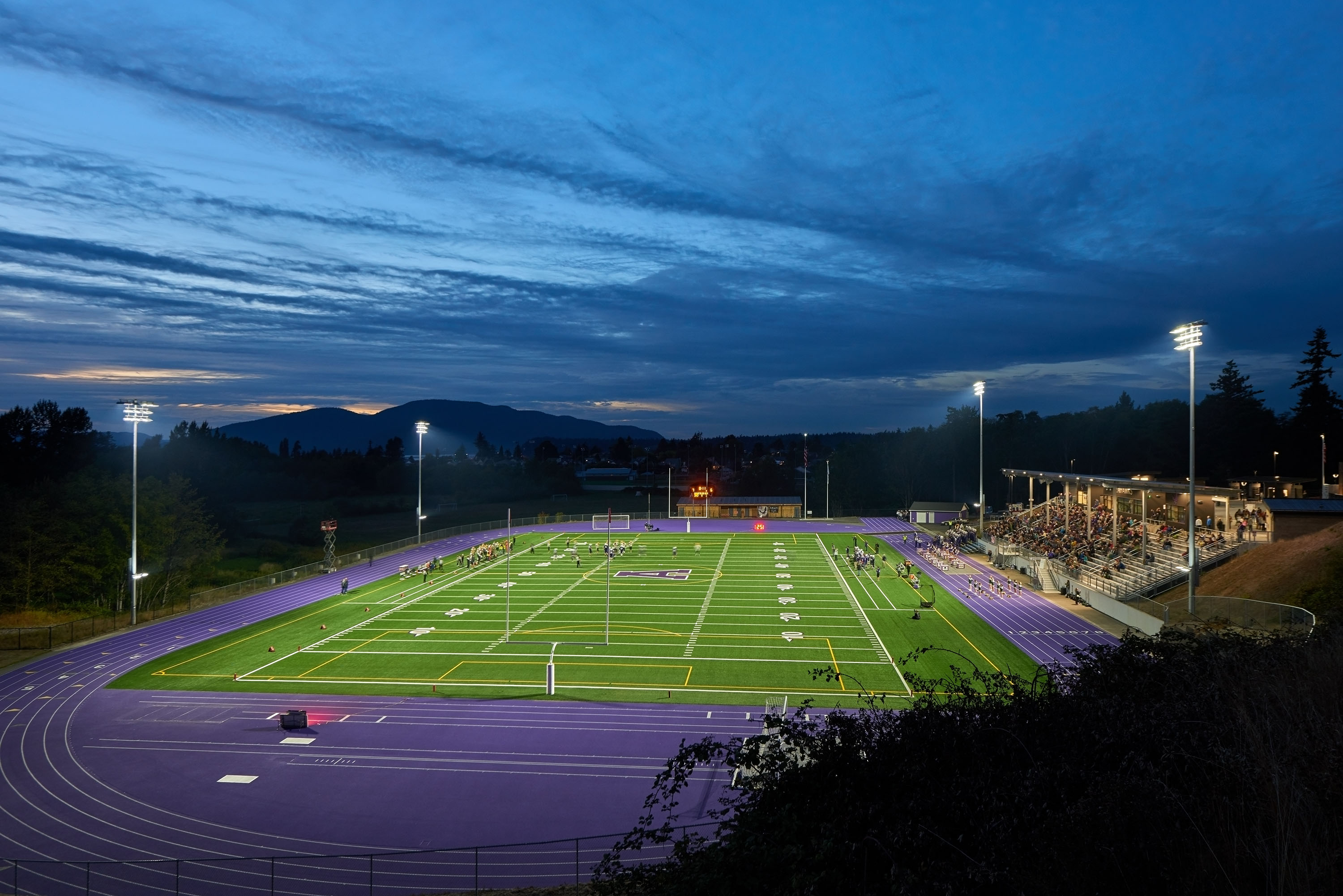 An overview photo of a football game with stadium lights lighting the field.