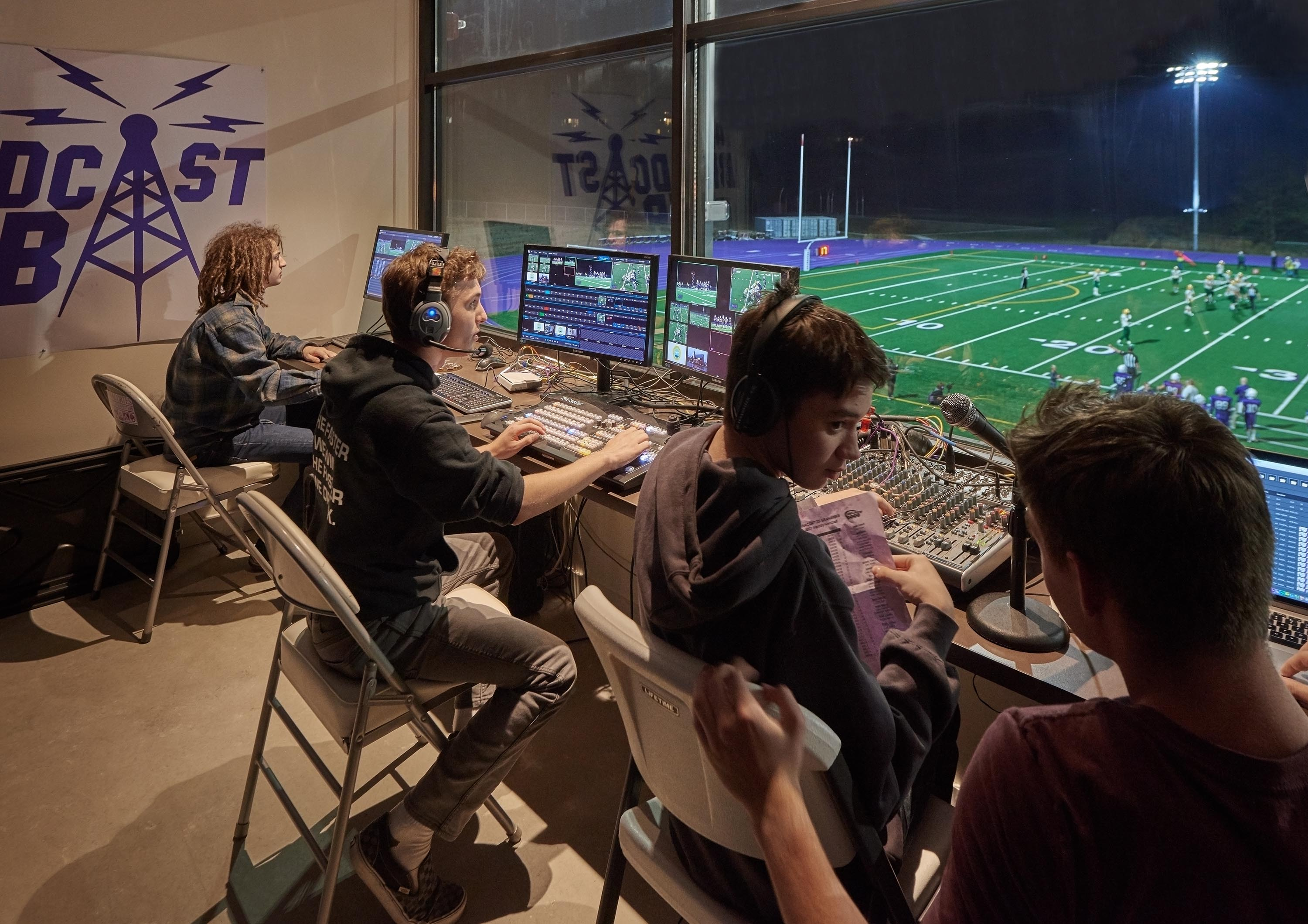 Students in the broadcast room overlooking the football game.