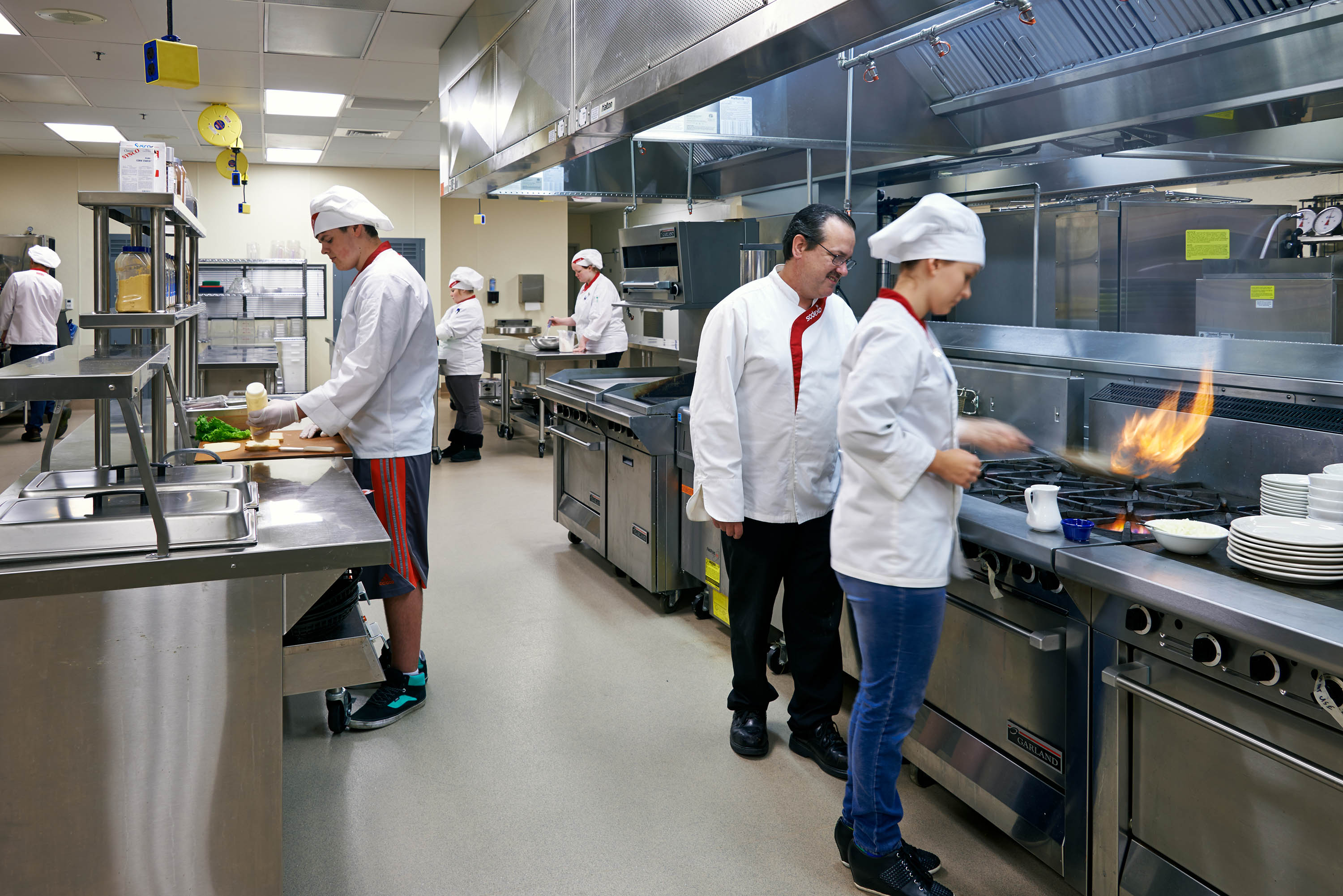 A teacher and students learning in the culinary kitchen.