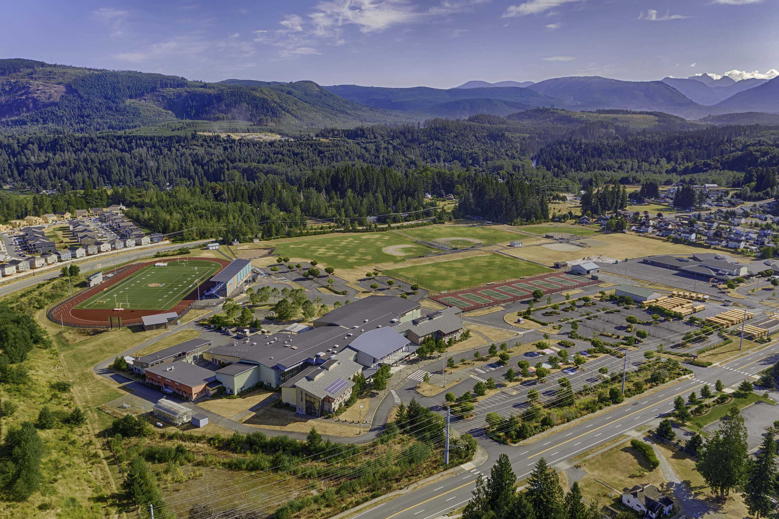 Aerial view of the campus, athletic field, and mountains off in the distance.