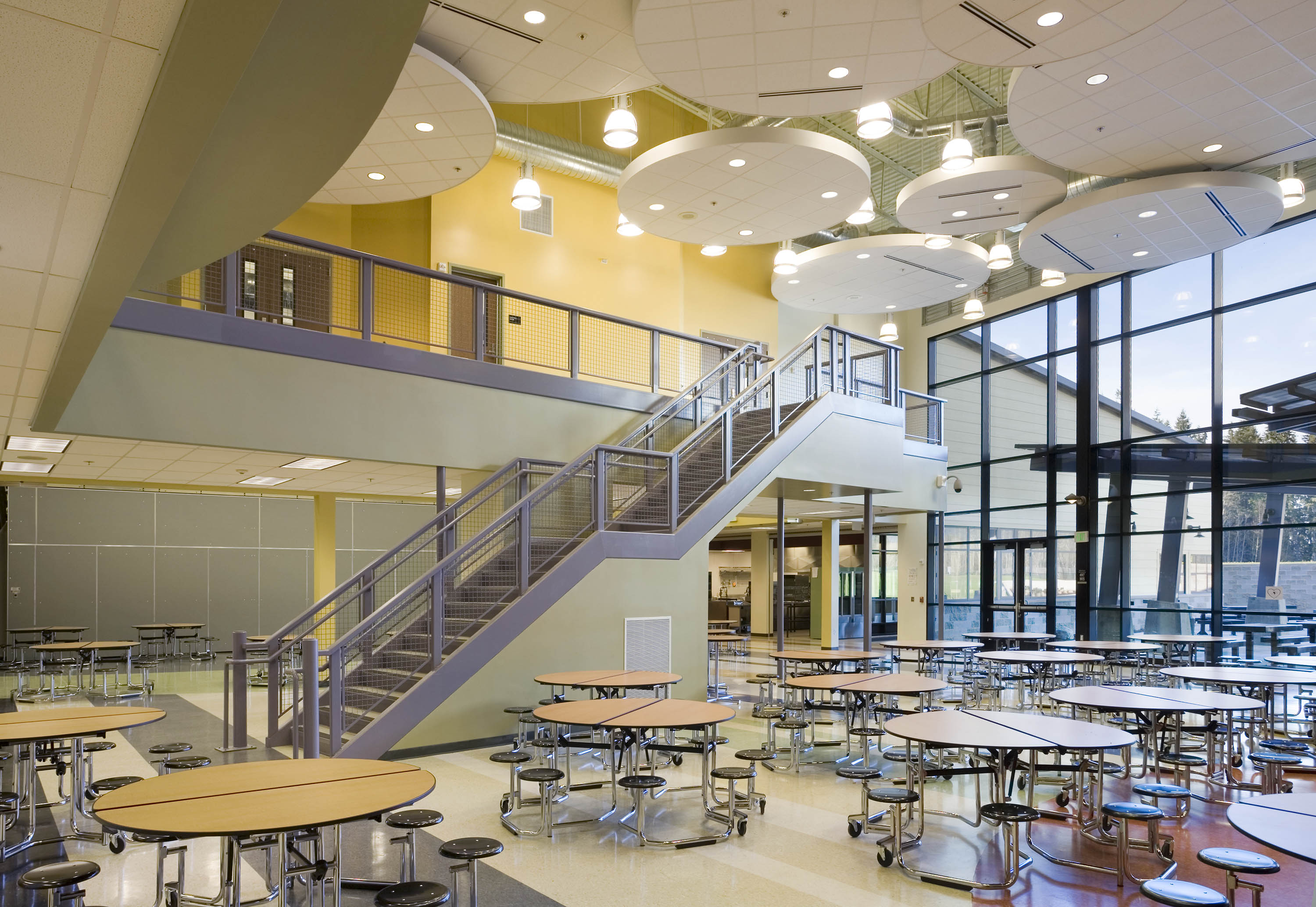 Commons area with tables and chairs set up and the stairs to the second floor.